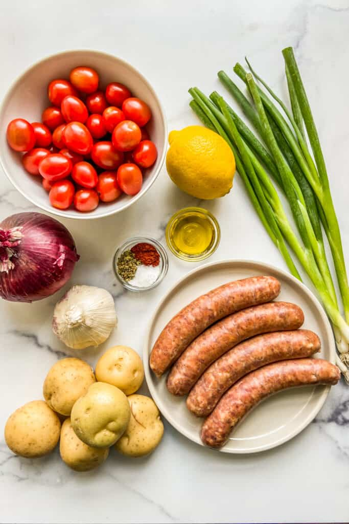 Italian sausage, potatoes, cherry tomatoes, a red onion, a lemon, spices, oil, and green onions on a marbled background.