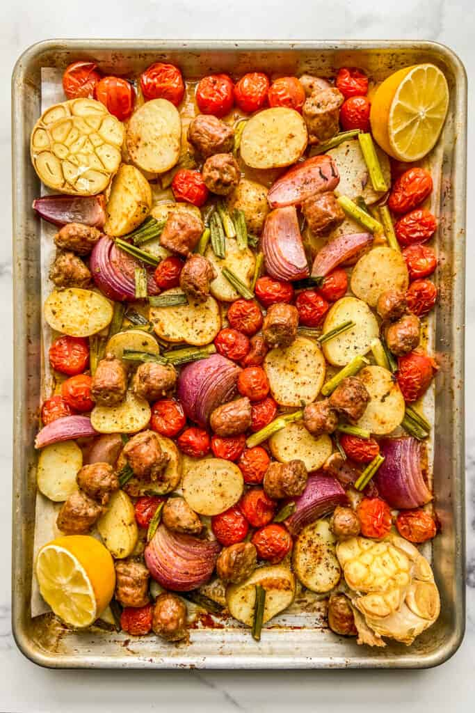 An overhead shot of a tray of roasted Italian sausage, potatoes, tomatoes, and other veggies.