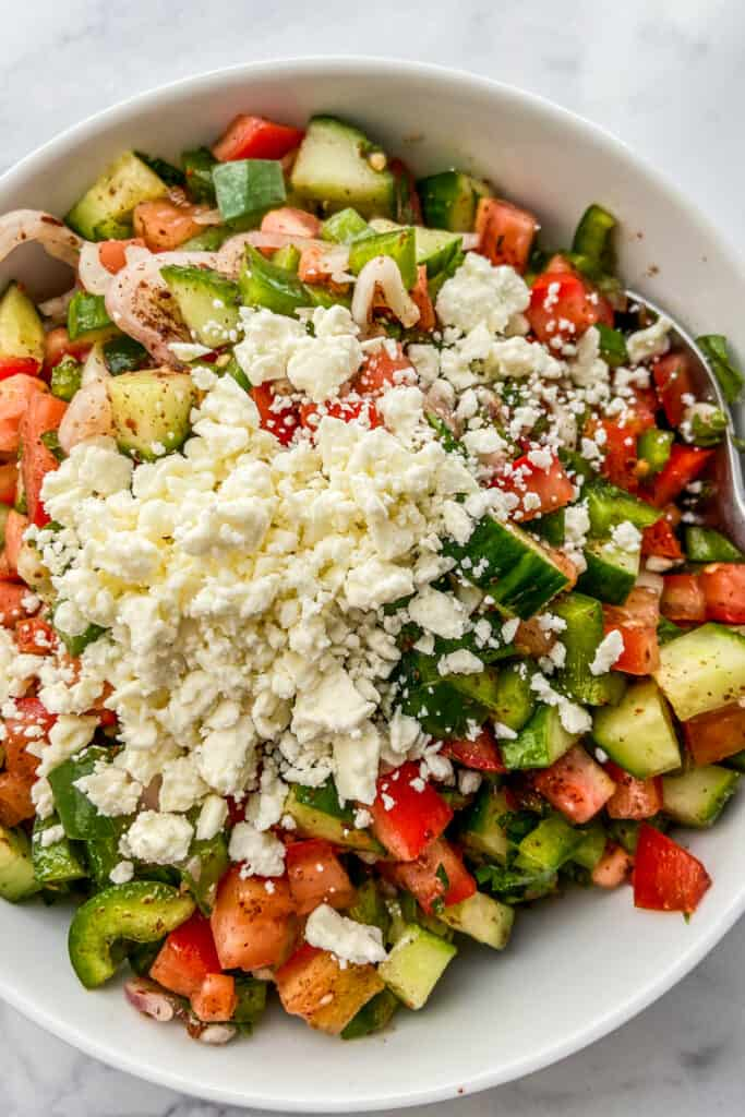 An overhead shot of a bowl of Turkish chopped salad topped with crumbled feta cheese.