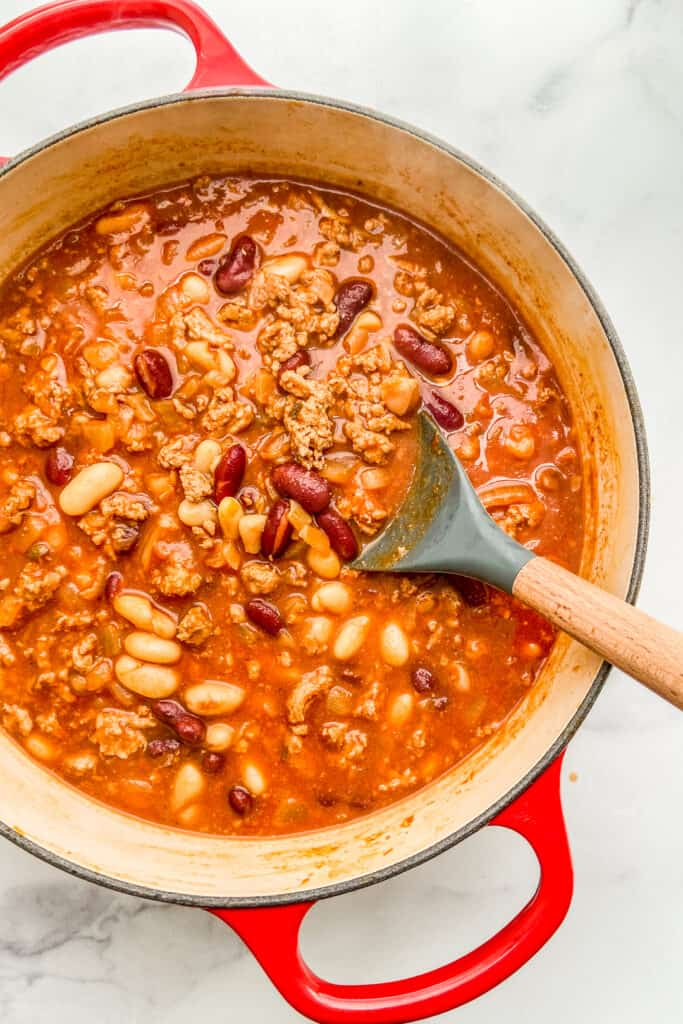 An overhead shot of a red dutch oven with ground turkey chili and a wooden spoon.
