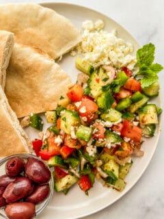 Turkish shepherds salad on a plate with kalamata olives and pita bread.