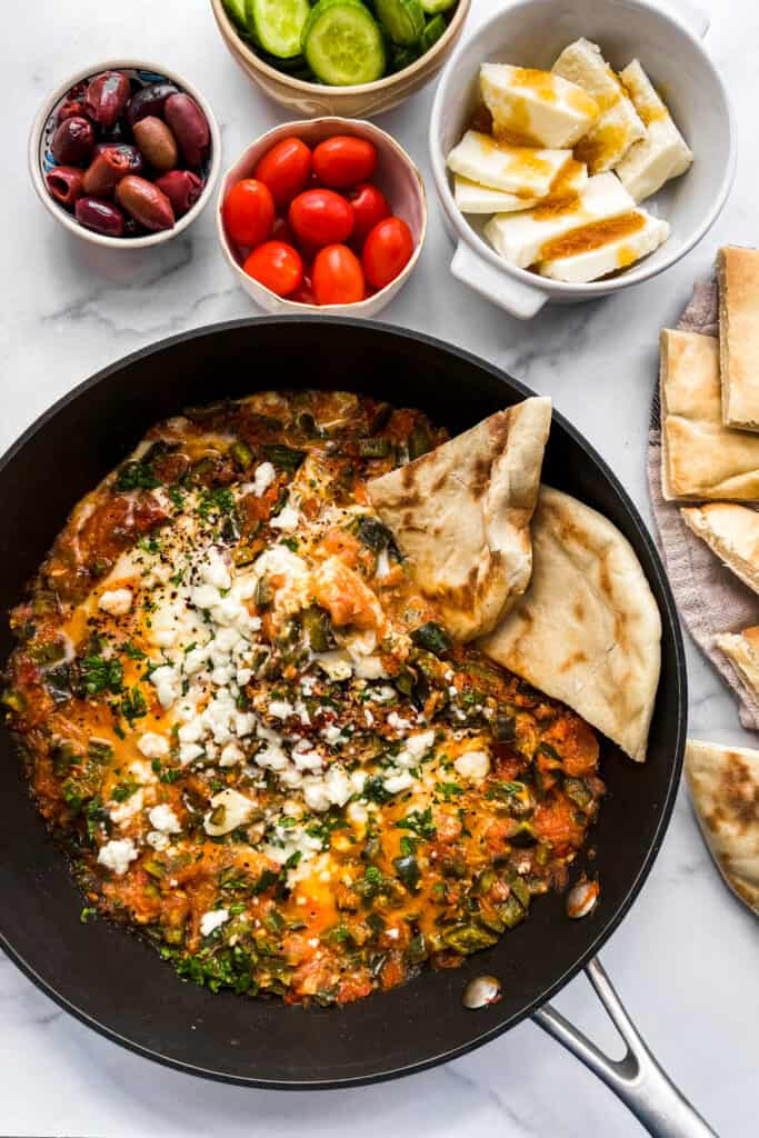 A skillet with menemen, next to some sliced pita, cheese, olives, cherry tomatoes, and sliced cucumber.