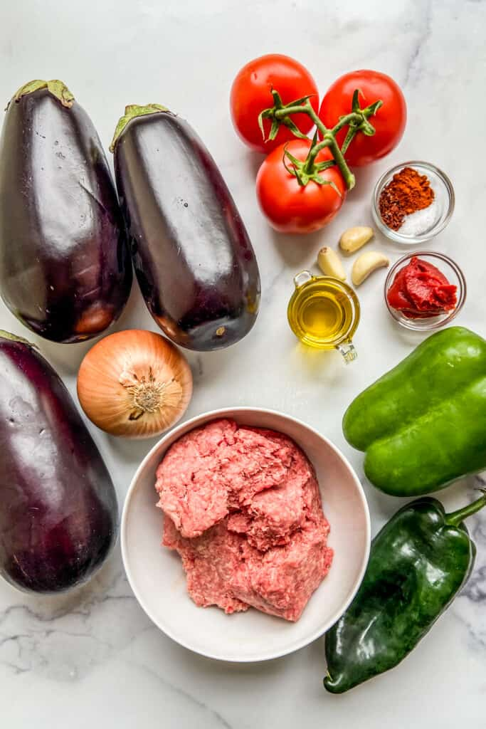 Eggplants, ground beef, a yellow onion, tomatoes, green peppers, tomato paste, garlic cloves, spices, and olive oil on a marble background.