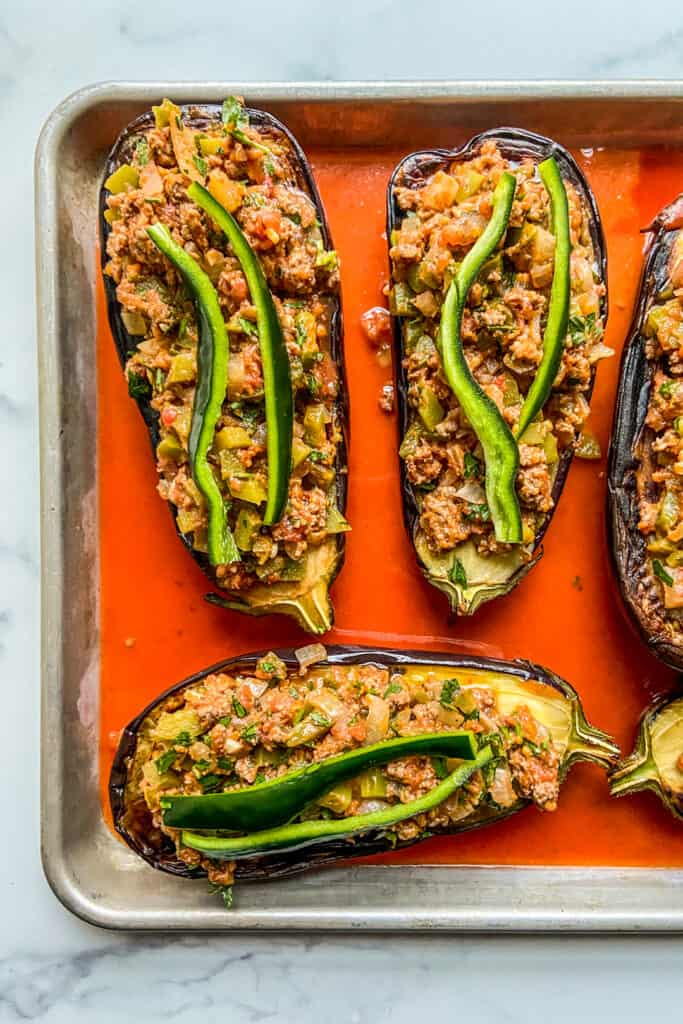 Stuffed eggplants on a baking sheet in a tomato sauce, before going in the oven.