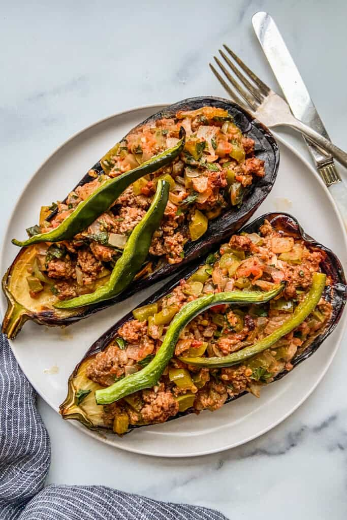 Two stuffed eggplants on a white plate, next to a fork and knife.