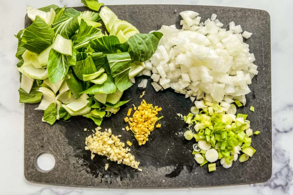 Chopped bok choy, diced onions, chopped green onions, minced garlic, and minced ginger on a black cutting board.